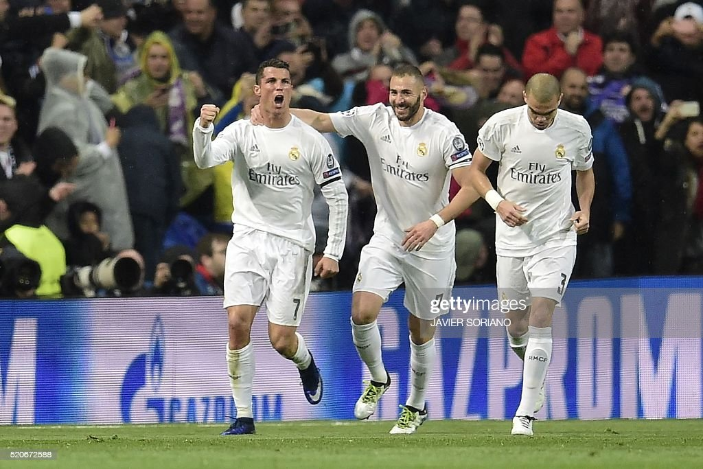 Real Madrid's Portuguese forward Cristiano Ronaldo (L), Real Madrid's French forward Karim Benzema (C) aqnd Real Madrid's Portuguese defender Pepe celebrate after scoring second during the Champions League quarter-final second leg football match Real Madrid vs Wolfsburg at the Santiago Bernabeu stadium in Madrid on April 12, 2016. / AFP / JAVIER