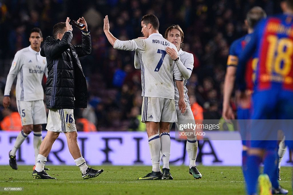 Real Madrid's Portuguese forward Cristiano Ronaldo (C), Real Madrid's Croatian midfielder Luka Modric (R) and teammates celebrate their 1-1 draw at the end of the Spanish league football match FC Barcelona vs Real Madrid CF at the Camp Nou stadium in Barcelona on December 3, 2016. / AFP / JOSEP