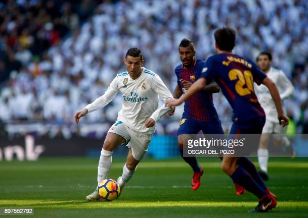 Real Madrid's Portuguese forward Cristiano Ronaldo runs with the ball during the Spanish League 'Clasico' football match Real Madrid CF vs FC...