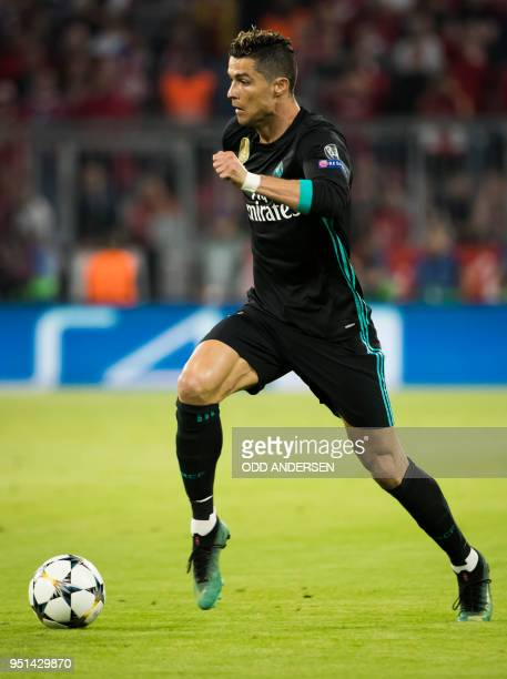 Real Madrid's Portuguese forward Cristiano Ronaldo runs with the ball during the UEFA Champions League semifinal firstleg football match FC Bayern...