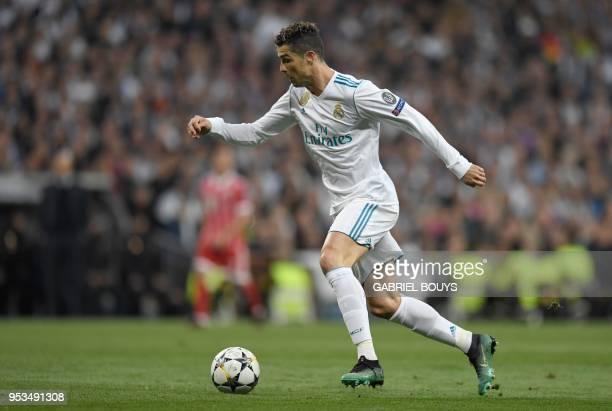 Real Madrid's Portuguese forward Cristiano Ronaldo runs with the ball during the UEFA Champions League semifinal secondleg football match Real Madrid...