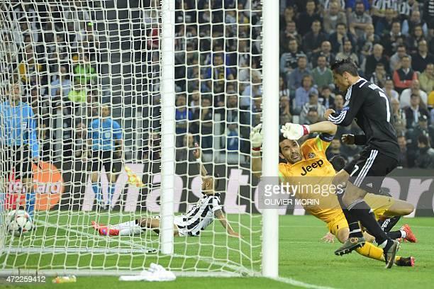Real Madrid's Portuguese forward Cristiano Ronaldo scores against Juventus' goalkeeper and captain Gianluigi Buffon during the UEFA Champions League...