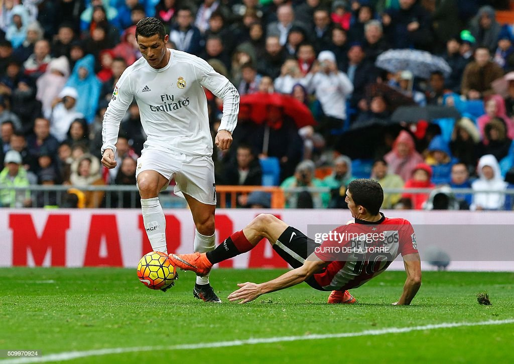 Real Madrid's Portuguese forward Cristiano Ronaldo (L) scores during the Spanish league football match Real Madrid CF vs Athletic Club Bilbao at the Santiago Bernabeu stadium in Madrid on February 13, 2016. / AFP / CURTO