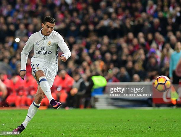 TOPSHOT Real Madrid's Portuguese forward Cristiano Ronaldo scores during the Spanish league football match Club Atletico de Madrid vs Real Madrid CF...