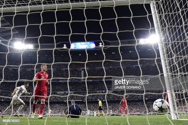 Real Madrid's Portuguese forward Cristiano Ronaldo scores his third goal during the UEFA Champions League quarterfinal second leg football match Real...