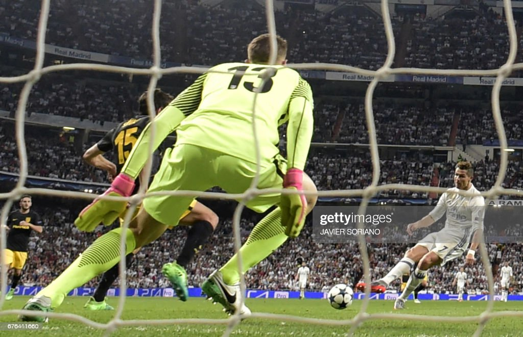 Real Madrid's Portuguese forward Cristiano Ronaldo (R) scores his third goal during the UEFA Champions League semifinal first leg football match Real Madrid CF vs Club Atletico de Madrid at the Santiago Bernabeu stadium in Madrid, on May 2, 2017. /