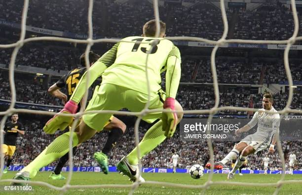 Real Madrid's Portuguese forward Cristiano Ronaldo scores his third goal during the UEFA Champions League semifinal first leg football match Real...