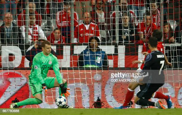 Real Madrid's Portuguese forward Cristiano Ronaldo scores the 12 goal past Bayern Munich's goalkeeper Manuel Neuer during the UEFA Champions League...