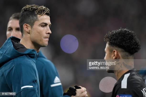 Real Madrid's Portuguese forward Cristiano Ronaldo shakes hands with Paris SaintGermain's Brazilian forward Neymar before the UEFA Champions League...