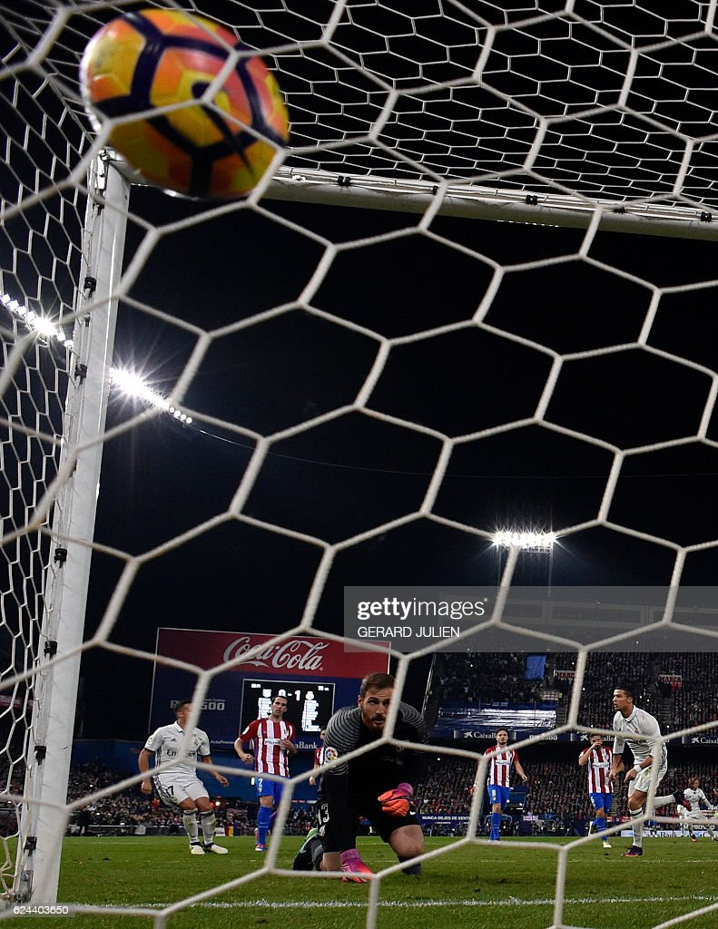 Real Madrid's Portuguese forward Cristiano Ronaldo (R) shoots a penalty kick to score a goal during the Spanish league football match between Club Atletico de Madrid and Real Madrid CF at the Vicente Calderon stadium in Madrid, on November 19, 2016. / AFP / GERARD