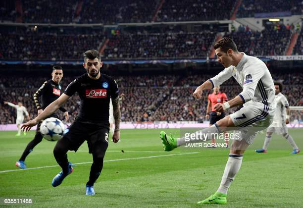 Real Madrid's Portuguese forward Cristiano Ronaldo shoots as he vies with Napoli's midfielder Lorenzo Insigne during the UEFA Champions League round...