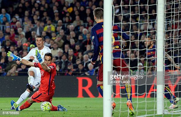 Real Madrid's Portuguese forward Cristiano Ronaldo shoots next to Barcelona's Chilean goalkeeper Claudio Bravo to score a goal during the Spanish...