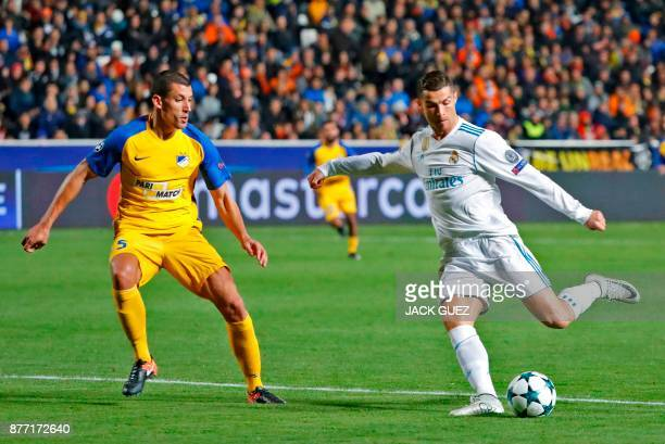 Real Madrid's Portuguese forward Cristiano Ronaldo shoots to score as he is marked by Apoel's Spanish midfielder Jesus Rueda during the UEFA...