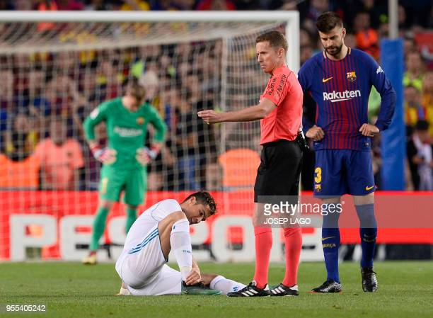 TOPSHOT Real Madrid's Portuguese forward Cristiano Ronaldo sits on the field after resulting injured dbeside Spanish referee Hernandez Hernandez and...