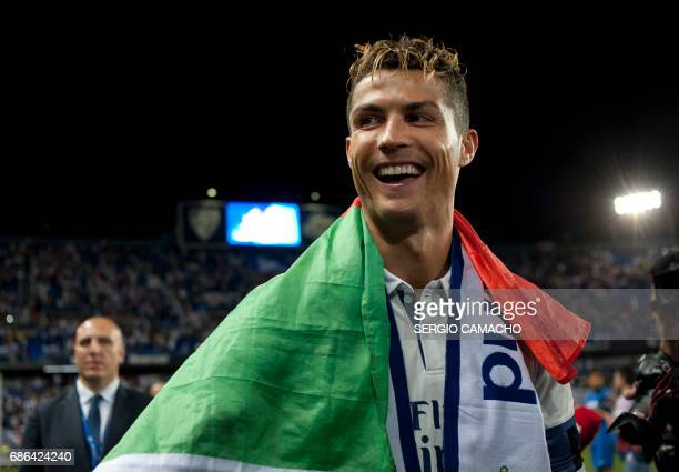 TOPSHOT Real Madrid's Portuguese forward Cristiano Ronaldo smiles as he celebrates at the end of the Spanish league football match Malaga CF vs Real...