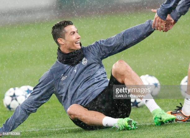 Real Madrid's Portuguese forward Cristiano Ronaldo smiles during a training session under heavy rain on the eve of the Champions League football...