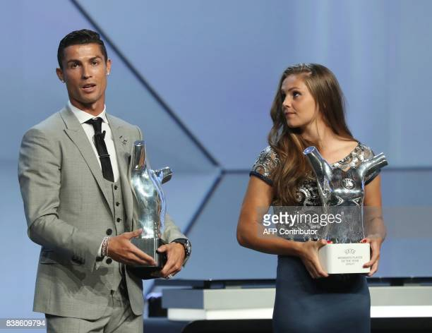 Real Madrid's Portuguese forward Cristiano Ronaldo speaks holding the trophy as Netherlands' midfielder Lieke Martens looks on after he was awarded...