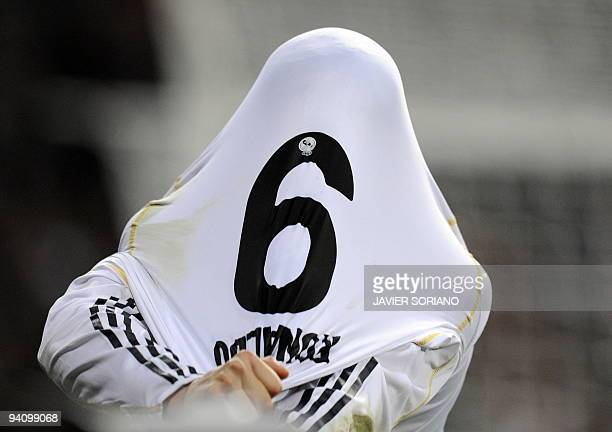 Real Madrid's Portuguese forward Cristiano Ronaldo takes his jersey off after scoring against Almeria during a Spanish league football match at...