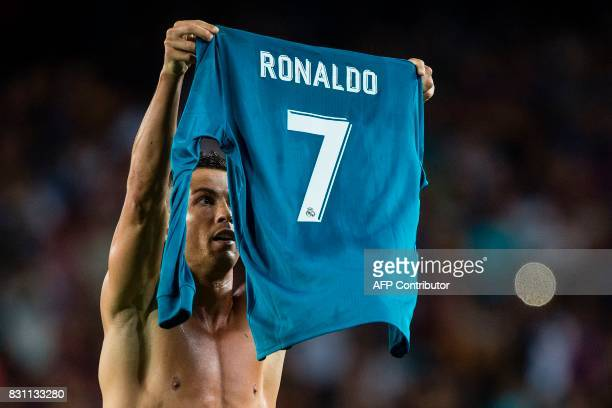 Real Madrid's Portuguese forward Cristiano Ronaldo takes off his jersey to celebrate his goal during the first leg of the Spanish Supercup football...