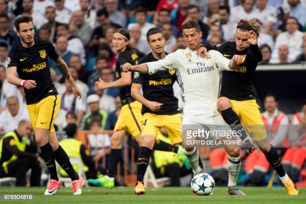 TOPSHOT Real Madrid's Portuguese forward Cristiano Ronaldo vies with Atletico Madrid's midfielder Gabi and Atletico Madrid's French forward Antoine...