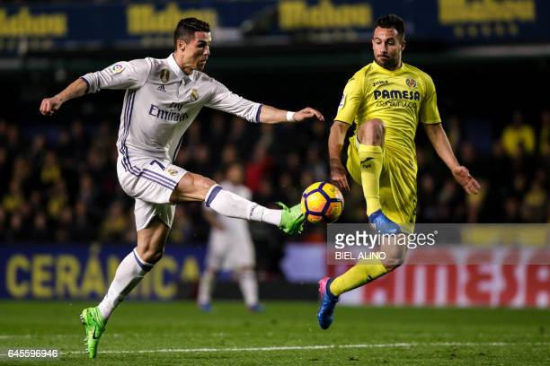 TOPSHOT Real Madrid's Portuguese forward Cristiano Ronaldo vies with Villareal's defender Mario Gaspar during the Spanish League football match...