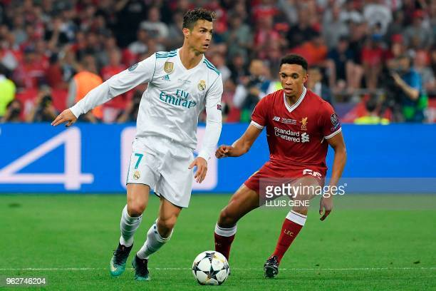 Real Madrid's Portuguese forward Cristiano Ronaldo vies with Liverpool's English defender Trent AlexanderArnold during the UEFA Champions League...