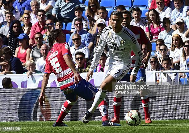 Real Madrid's Portuguese forward Cristiano Ronaldo vies with Granada's Chilean midfielder Manuel Rolando Iturra during the Spanish league football...