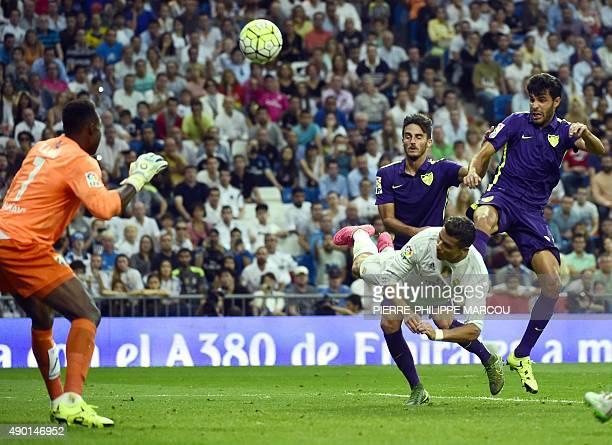 Real Madrid's Portuguese forward Cristiano Ronaldo vies with Malaga's defender Miguel Torres during the Spanish league football match Real Madrid CF...