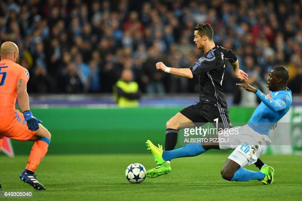 Real Madrid's Portuguese forward Cristiano Ronaldo vies with Napoli's defender from France Kalidou Koulibaly and Napoli's goalkeeper from Spain Pepe...