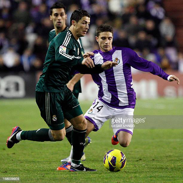 Real Madrid's Portuguese forward Cristiano Ronaldo vies with Valladolid's midfielder Omar Ramos during the Spanish league football match Real...