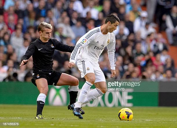 Real Madrid's Portuguese forward Cristiano Ronaldo vies with Real Sociedad's French forward Antoine Griezmann during the Spanish league football...