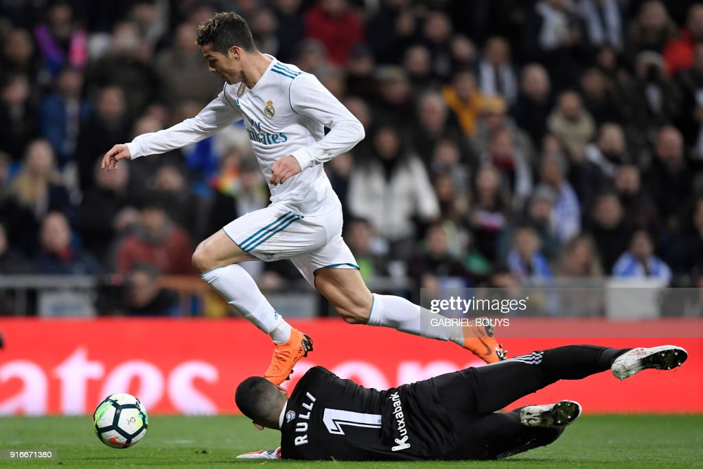 Real Madrid's Portuguese forward Cristiano Ronaldo (L) vies with Real Sociedad's Argentinian goalkeeper Geronimo Rulli during the Spanish league football match between Real Madrid CF and Real Sociedad at the Santiago Bernabeu stadium in Madrid on February 10, 2018. /