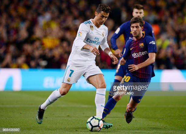 Real Madrid's Portuguese forward Cristiano Ronaldo vies with Barcelona's Spanish midfielder Sergi Roberto during the Spanish league football match...