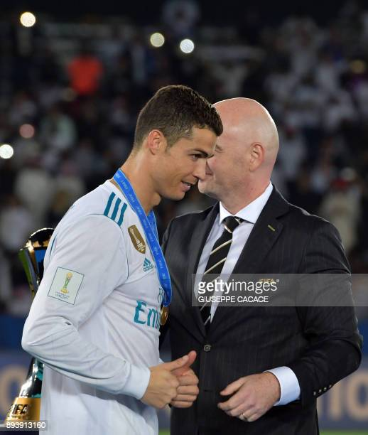 Real Madrid's Portuguese forward Ronaldo is presented a gold medal by FIFA President Gianni Infantino following the Club World Cup final football...