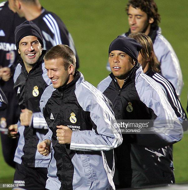 Real Madrid's Portuguese Luis Figo runs next to his teammates British David Beckham and Brazilian Ronaldo during the first training session after the...