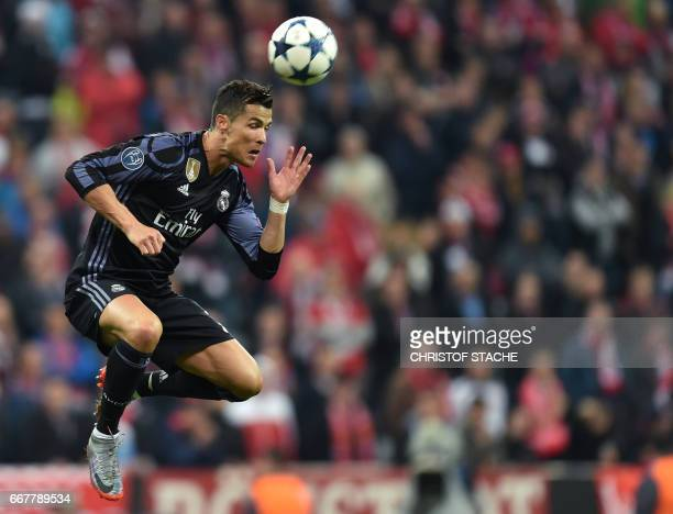 TOPSHOT Real Madrid's Portuguese striker Cristiano Ronaldo heads the ball during the UEFA Champions League 1st leg quarterfinal football match FC...