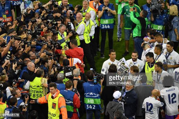Real Madrid's Portuguese striker Cristiano Ronaldo hold the trophy next to photographers and real madrid players after the UEFA Champions League...
