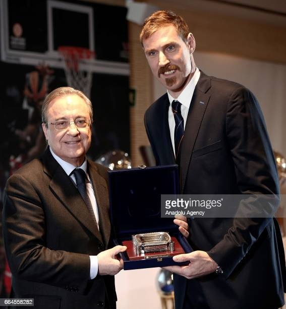 Real Madrid's president Florentino Perez and Real Madrid's Argentinian forward Andres Nocioni gives a plaque during a press conference organised by...