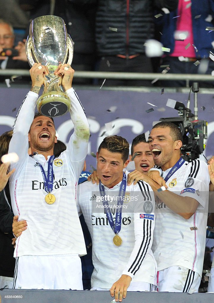Real Madrid's Sergio Ramos (L), Cristiano Ronaldo (C) and Pepe (R) celebrate with the trophy after winning the UEFA Super Cup football match between Real Madrid and FC Sevilla on August 12, 2014 at Cardiff City Stadium in Cardiff, Wales on August 12, 2014.