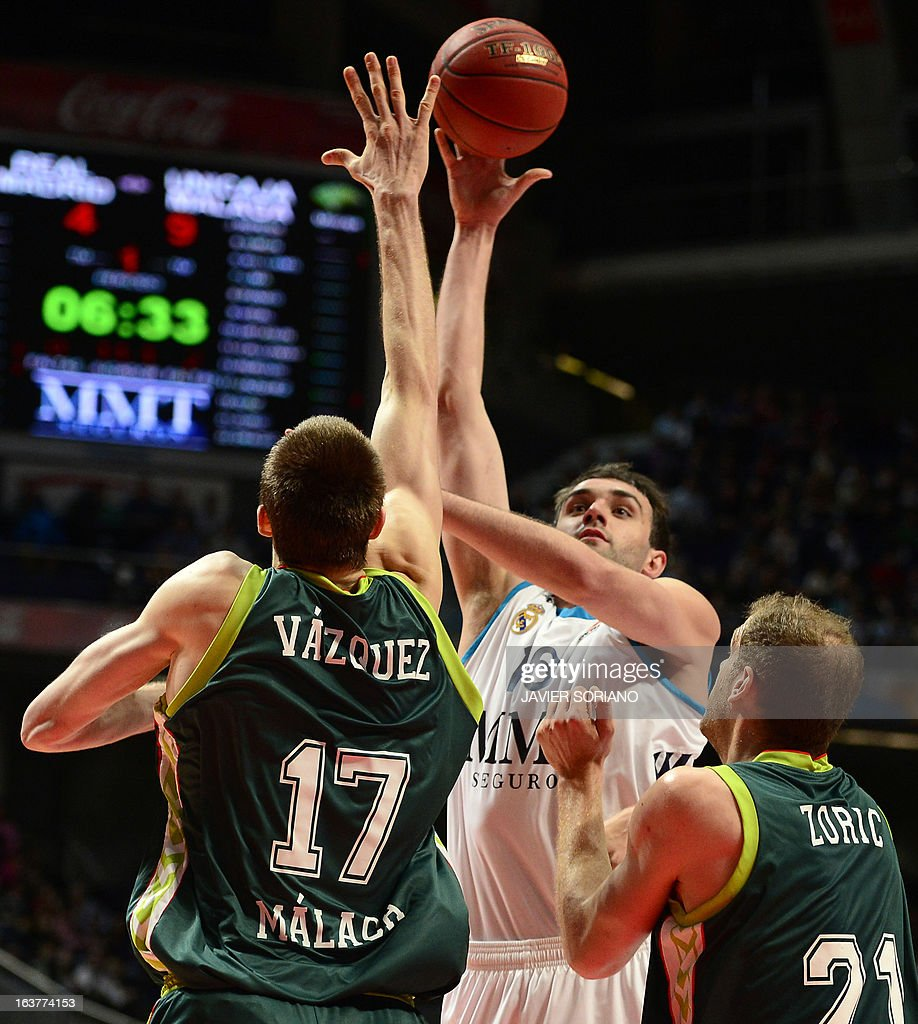 Real Madrid's Slovenian centre Mirza Begic (C) vies with Unicaja's centre Fran Vazquez (L) and Unicaja's Croatian centre Luka Zoric during the Euroleague basketball match Real Madrid vs Unicaja Malaga at the Palacio de los Deportes in Madrid on March 15, 2013.