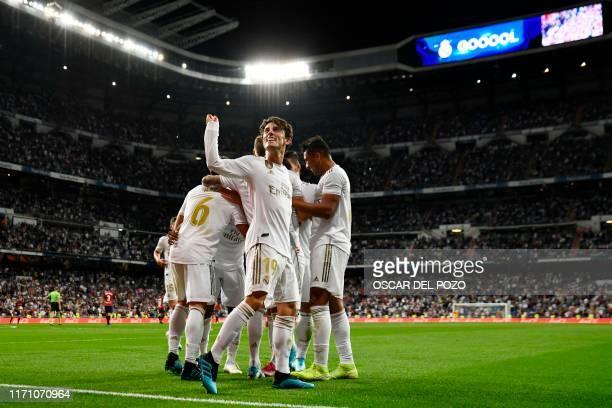 Real Madrid's Spanish defender Alvaro Odriozola and teammates celebrate their second goal scored by Real Madrid's Brazilian forward Rodrygo during...