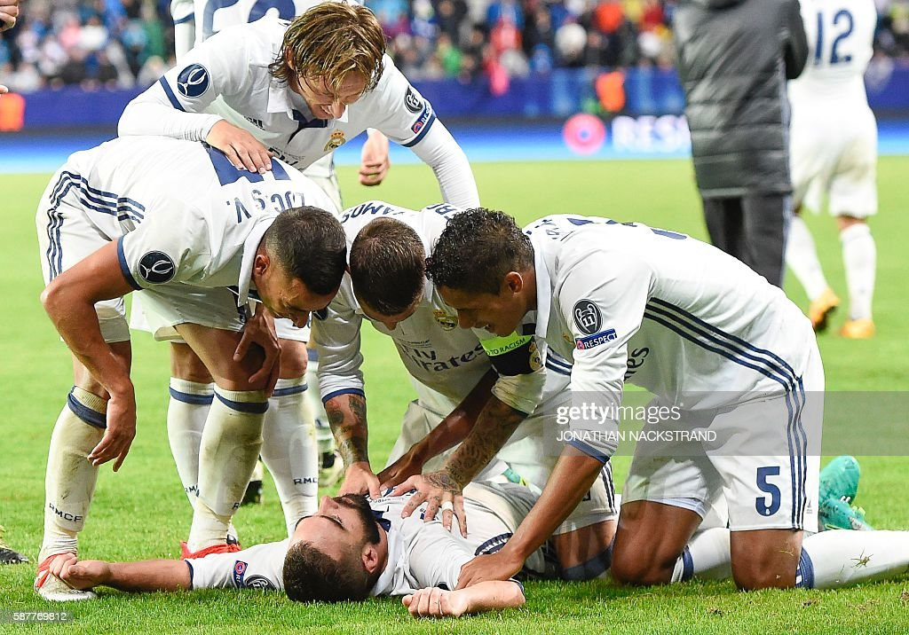 Real Madrid's Spanish defender Dani Carvajal (C) celebrates with his teammates after scoring the 3-2 goal at overtime during the UEFA Super Cup final football match between Real Madrid CF and Sevilla FC on August 9, 2016 at the Lerkendal Stadion in Trondheim. Real Madrid won 3-2. / AFP / JONATHAN