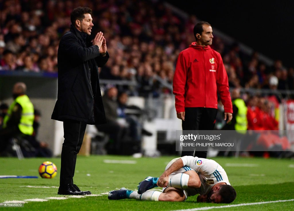 Real Madrid's Spanish defender Dani Carvajal (bottom) groans beside Atletico Madrid's Argentinian coach Diego Simeone (L) during the Spanish league football match Atletico Madrid vs Real Madrid at the Wanda Metropolitan stadium in Madrid on November 18, 2017. /