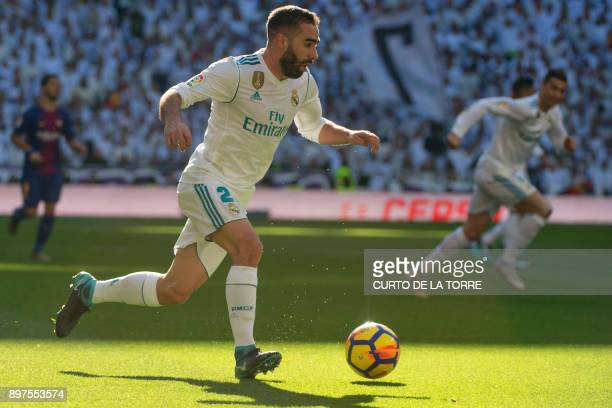 Real Madrid's Spanish defender Dani Carvajal runs with the ball during the Spanish League Clasico football match Real Madrid CF vs FC Barcelona at...