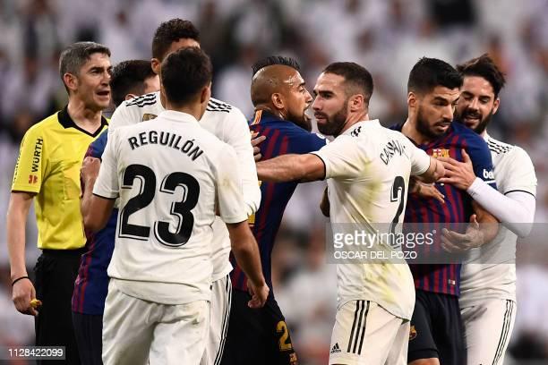 Real Madrid's Spanish defender Dani Carvajal separates Barcelona's Uruguayan forward Luis Suarez and Real Madrid's Spanish defender Sergio Reguilon...