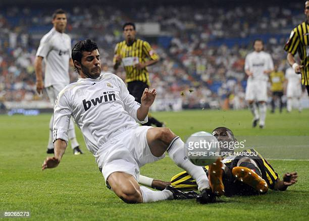 Real Madrid's Spanish defender Miguel Torres vies with AlIttihad's defender Hamad Almontashari during their Peace Cup football match at Santiago...