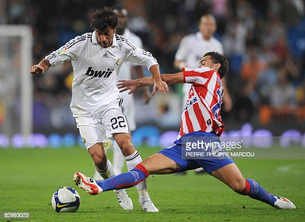 Real Madrid's Spanish defender Miguel Torres vies with Sporting's Spanish forward David Barral Torres during their Liga football match Santiago...