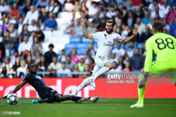 TOPSHOT Real Madrid's Spanish defender Nacho Fernandez challenges Club Brugge's Angolan defender Clinton Mata and Club Brugge's Belgian goalkeeper...