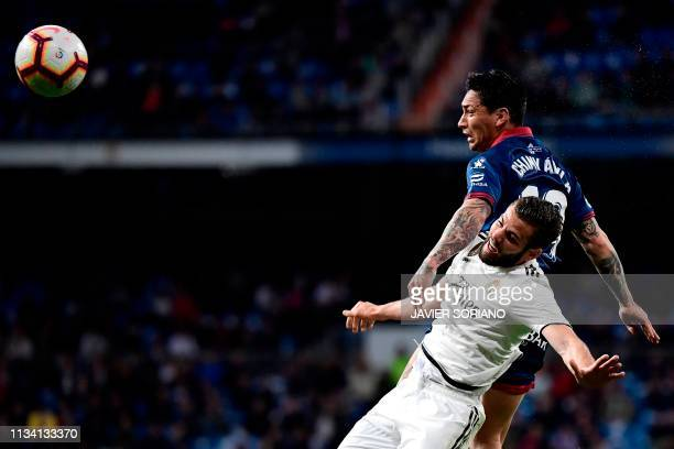 Real Madrid's Spanish defender Nacho Fernandez heads the ball with SD Huesca's Argentinian forward Chimy Avila during the Spanish League football...