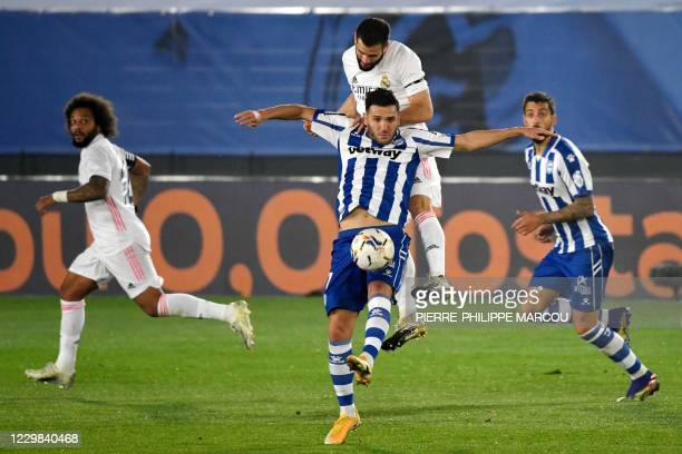 Real Madrid's Spanish defender Nacho Fernandez vies with Alaves' Spanish midfielder Luis Rioja during the Spanish League football match between Real...